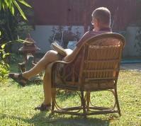 Lesender Mann in Gartenstuhl