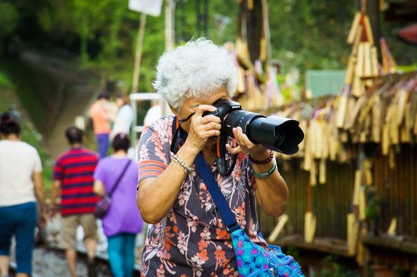 Das Bild zeigt eine reisende Seniorin ausgerüstet mit Fotoapparat und Teleobjektiv.