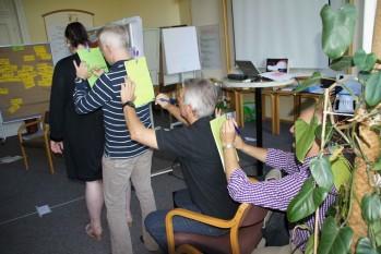 Mehrer Menschen sitzen und stehen hintereinander und beschriften gegenseitig Zettel auf ihren Rücken. au