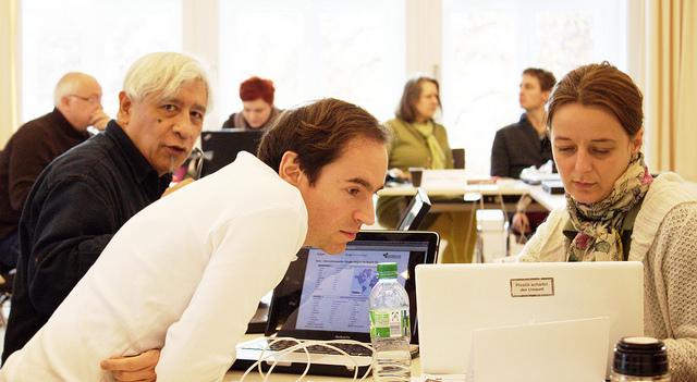 Menschen am Laptop in einem Seminarraum