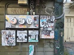 Mit Graffiti bekritzelte Kästen an einer Hauswand.