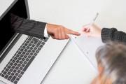 Das Bild zeigt einen Laptop, aus dem eine Hand ragt und auf den Schreibblock einer Person zeigt, die vor dem Laptop gerade etwas notieren möchte.
