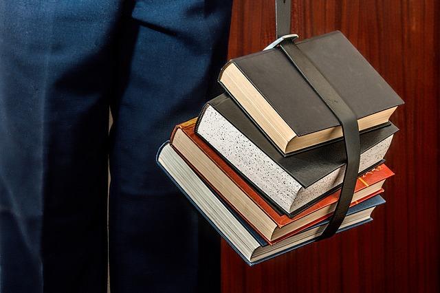 Das Bild zeigt Bücher, die zum Tragen mit einem Gürtel zusammengebunden sind.