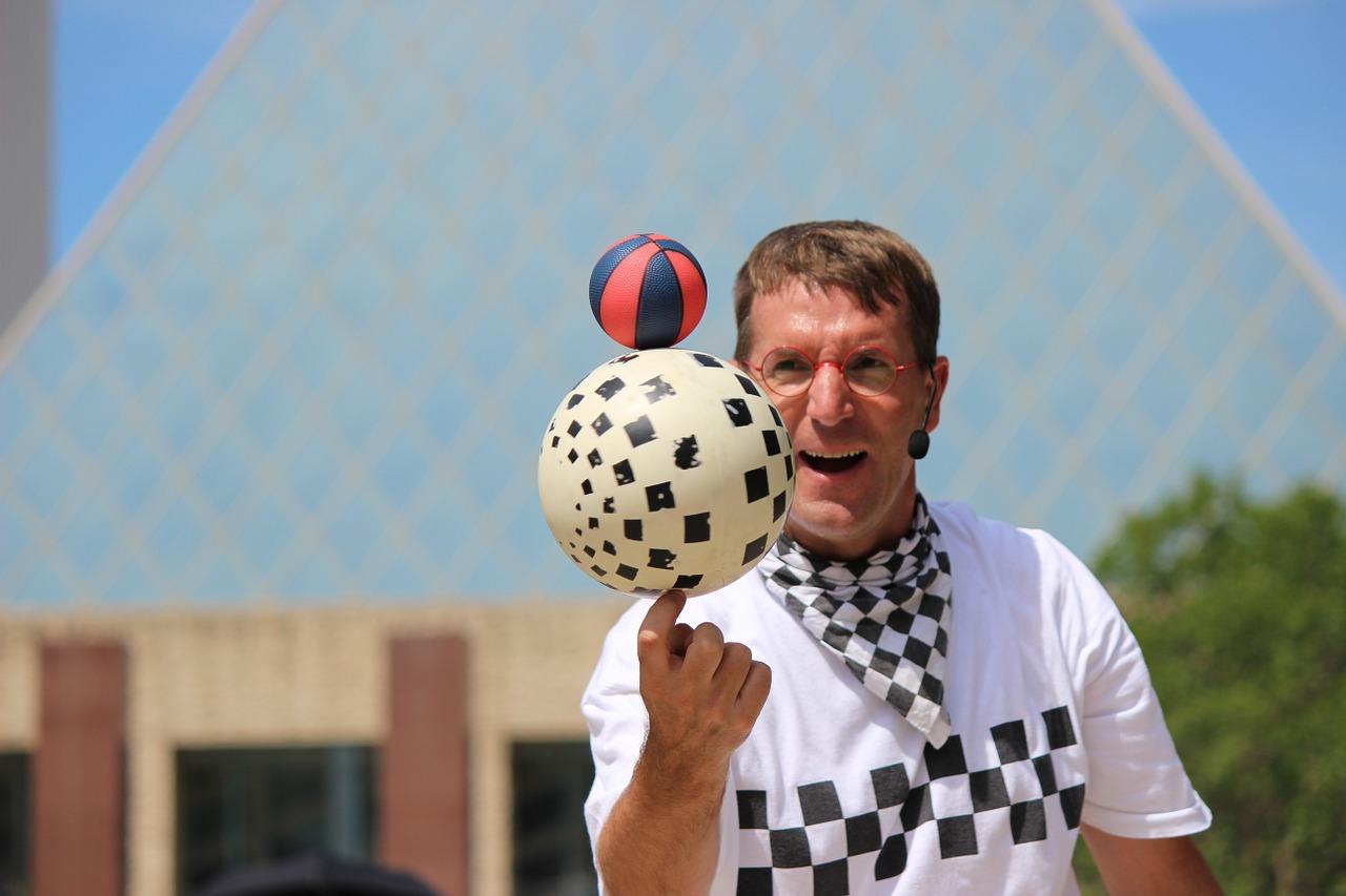 Mann vor einem Haus jongliert großen und kleinen Ball auf einer Finderspitze