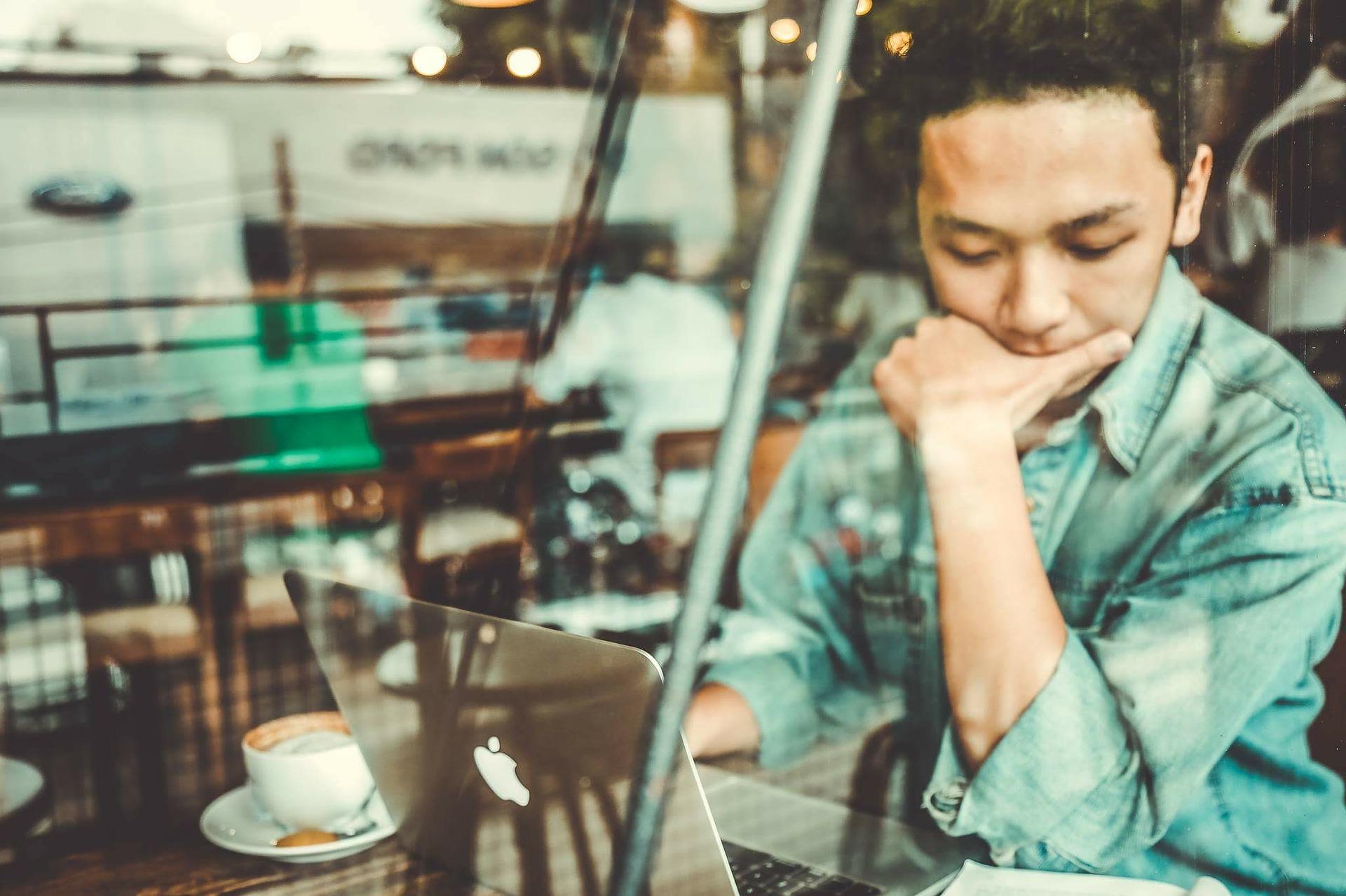 Das Bild zeigt einen Mann im Café mit seinem Laptop bei der Arbeit.