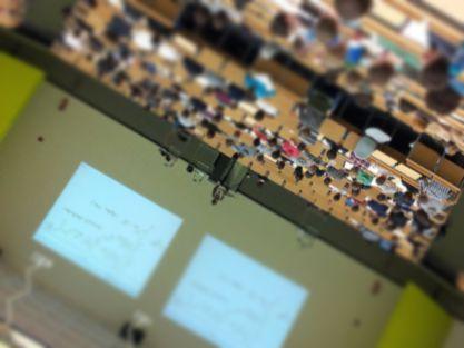 Schräg auf dem Kopf stehendes Foto von einem Hörsaal, teilweise unscharf