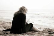 Ein Frau sitzt am Strand und liest.