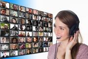 Das Bild zeigt eine junge Frau mit Headset, die auf einen Screen blickt, auf dem viele verschiedenen Videofenster von anderen Menschen abgebildet sind.