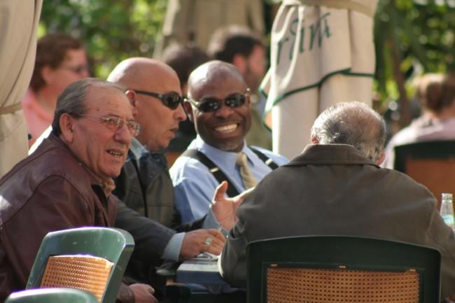 Männer an einem Tisch vor einem Café