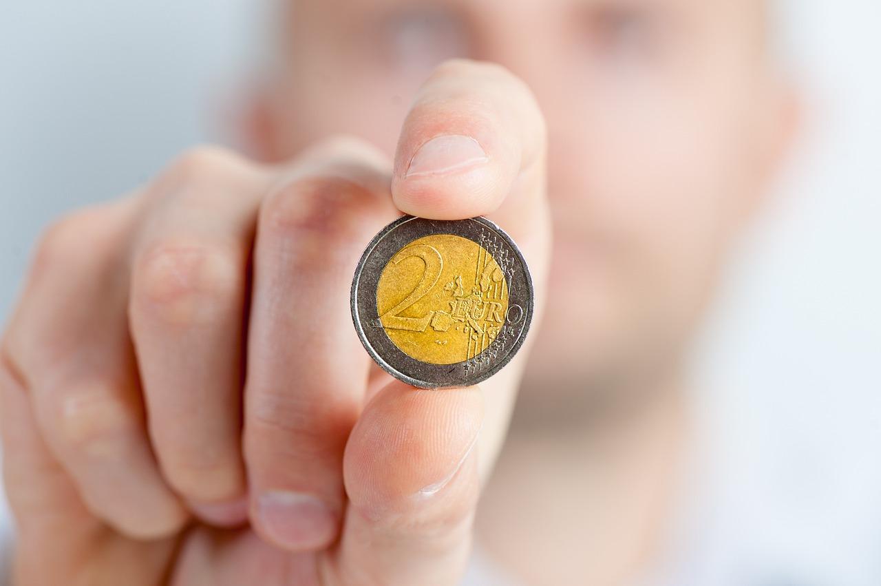 Das Bild zeigt einen Mann, der ein 2-Eurostück zeigt.
