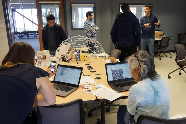Mehrere Personen unterhalten sich und arbeiten an Laptops in einem Maker Space.