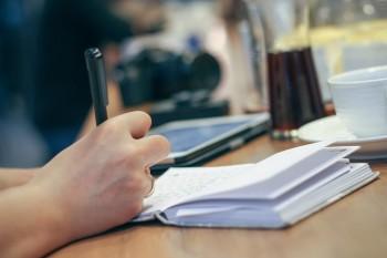 Hand schreibt mit Stift in ein Notizbuch, auf dem Tisch Kaffeetasse und Tablet