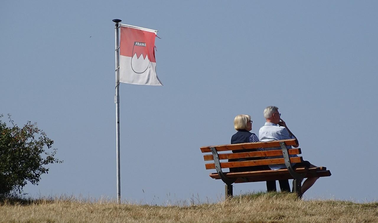 Das Bild zeigt ein älteres Paar von hinten auf einer Parkbank.