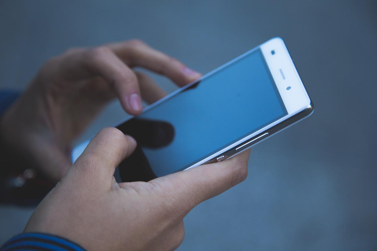 Das Bild zeigt ein Smartphone in den Händen einer Userin.