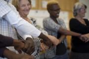 Das Bild zeigt einen Ausschnitt von Menschen, die in einem Kreis stehen und sich jeweils verschränkt an den Händen halten.