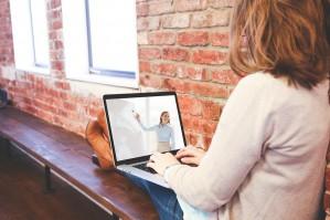 Das Bild zeigte eine Frau, die auf einer Bank sitzt und auf den Beinen ein Laptop hält, auf dem eine Lehrperson zu sehen ist, die etwas an einer Tafel zeigt.