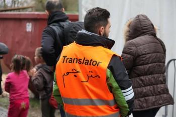 """Foto mit Menschen, einer trägt eine Warnweste auf der """"Translator"""" steht"""