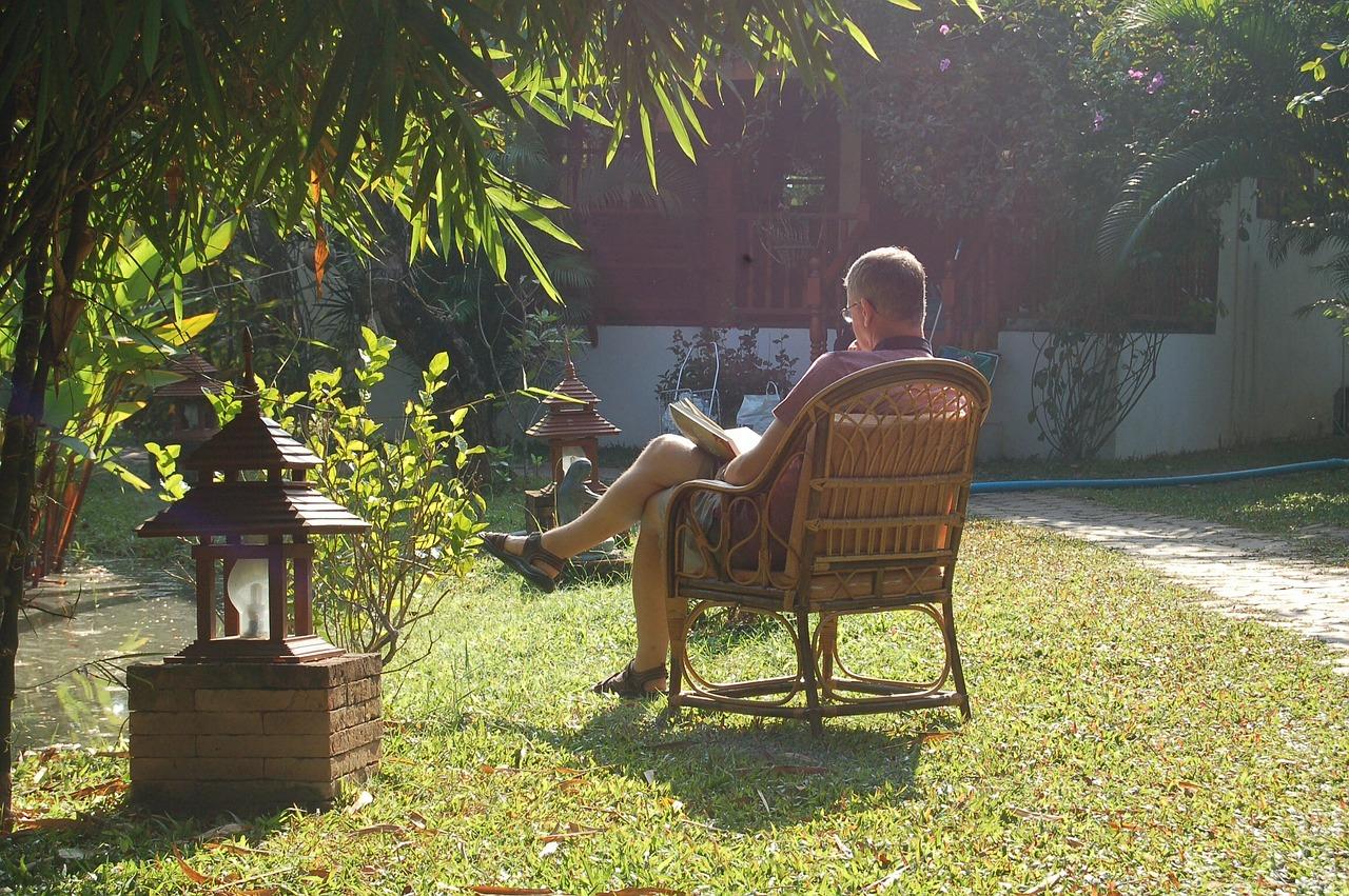 Mann im Korbsessel in einem asiatischen Garten