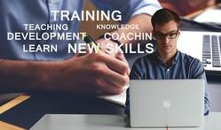 Ein Mann sitzt an einem MacBook. Hinter ihm erscheinen die Worte: Learn, New Skills, Coaching, Training
