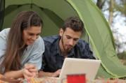 Das Symbolbild zeigt zwei Personen, die vor einem Zelt auf einer Decke liegen und in ein Laptop gucken.