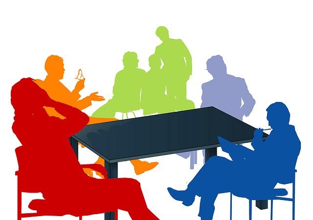 bunte Silhouetten von Menschen an einem Tisch.