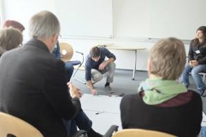 Das Bild zeigt mehrere Personen, die in einem Stuhlkreis sitzen. In der Mitte kniet eine Person und schreibt mit einem Stift auf ein großes weißes Plakat, das auf dem Boden liegt.