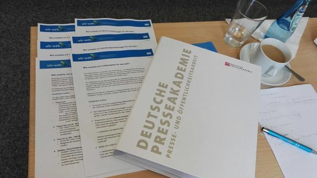 Diverse Unterlagen von der Deutschen Presseakademie und von wb-web liegen auf einem Tisch anlässlich eines Schreibworkshops