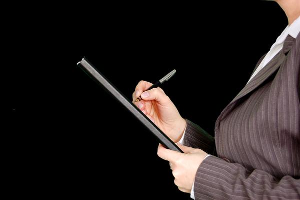 Eine Frau in einem Business-Anzug hat eine Mappe mit einem Blatt Papier in der Hand und notiert dort etwas mit einem Stift.