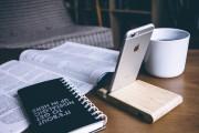 Das Bild zeigt ein Smartphone vor einer aufgeschlagenen Zeitschrift.