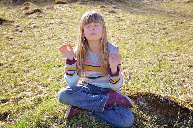 Mädchen sitzt im Schneidersitz auf der Erde, die Augen geschlossen, die Daumen und Zeigefinger zum Ring geschlossen.