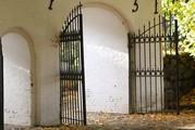 Geöffnetes Gittertor in einer weißen Mauer