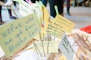 Das Bild zeigt bunte Moderationskarten, die voll beschrieben als kleine Fähnchen auf einem Tisch stehen.