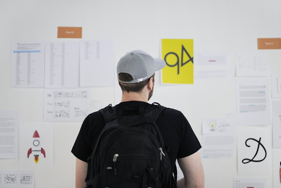 Ein Mann steht vor eine Informationswand seines Betriebes.
