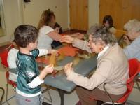Senioren und Kinder sind gemeinsam an einem Tisch und basteln.