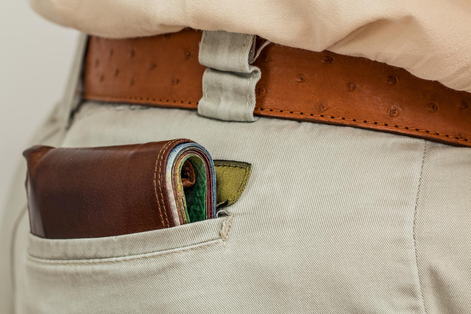 Das Bild zeigt eine gut gefüllte Geldbörse in einer Gesäßtasche.
