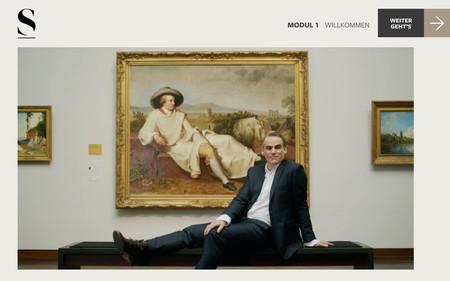 Mann sitzt vor einem Bild im Museum.