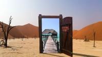 Eine offene Tür in der Wüste leitet an den Strand.