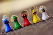 Das Bild zeigt fünf bunte Spielfiguren, die jeweils ein aufgemaltes Gesicht und aufgeklebte Haare haben.