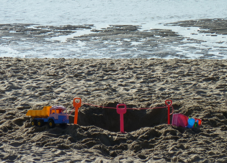Am Strand: Kinderspielzeug und eine tiefe Grube