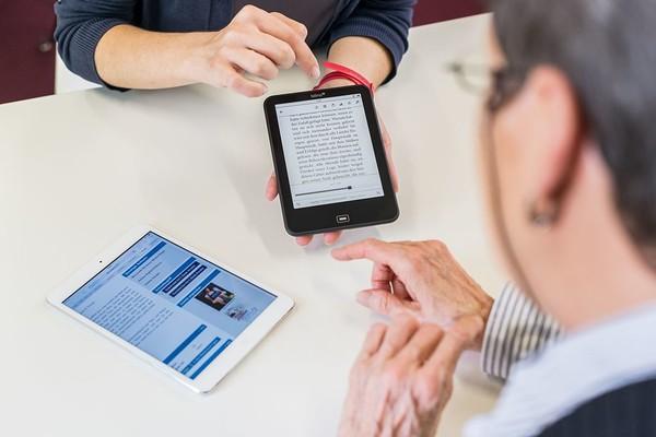 Schulung zum Umgang mit elektronischen Medien. Eine jüngere Person zeigt einer älteren Person die Bedienung eines E-Readers