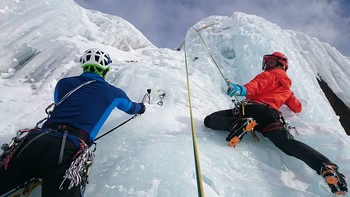 Zwei Kletterer mit Seilen in einem Gletscher