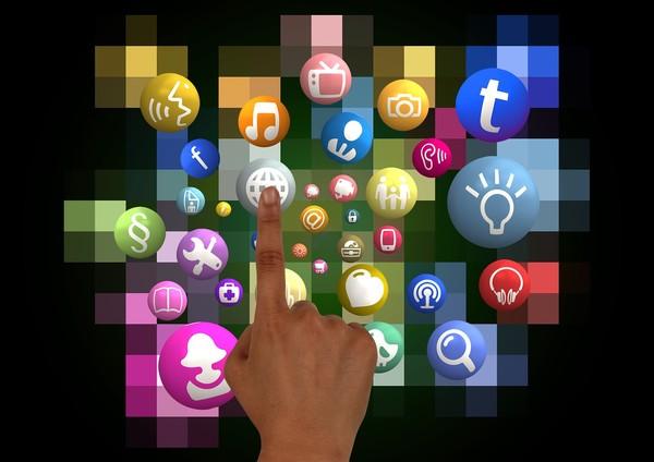 Ein Zeigefinger drückt auf einen Touchscreen mit vielen Icons