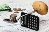 Ein Löffel balanciert Geld und Kartoffel auf einem Taschenrechner