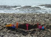 Strand: eine Grube mit Kinderspielzeug drumherum
