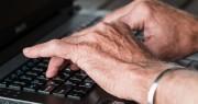 Das Bild zeigt die Hände einer älteren Person am Laptop.