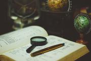 Das Bild zeigt ein aufgeschlagenes Sprachlernbuch mit Lupe und Stift.