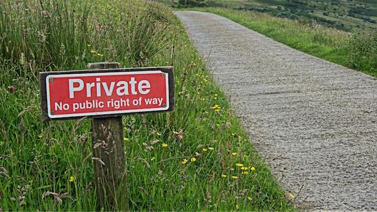 """Ein rotes Schild am Straßenrand mit der Aufschrift: """"Private. No public right of way""""."""