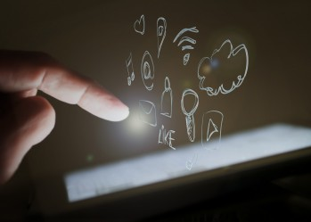 Finger zeigt auf Touchscreen, im Hintergrund Social Media Logos