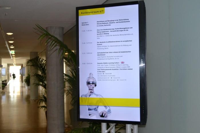 Ein Monitor vor einem Raum zeigt das Kongressprogramm auf der LEARNTEC