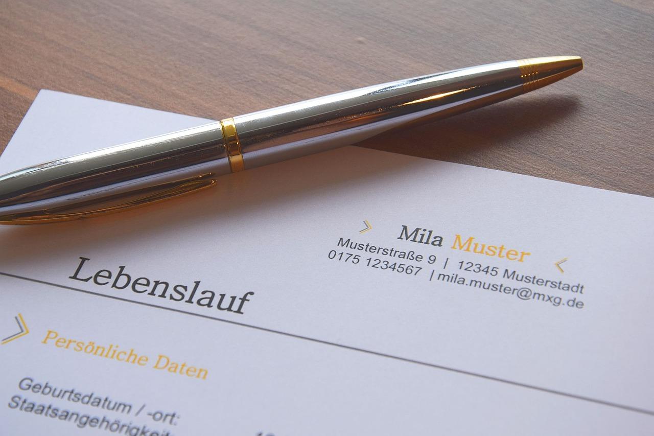 Das Bild zeigt einen Lebenslauf und einen Stift.